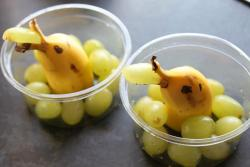 A snack where the banana and grapes are cut to look like a dolphin
