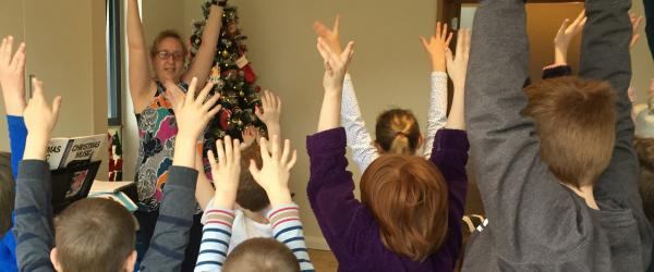 Big Sing- children warm up with their arms in the air
